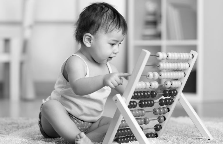 Cute baby boy playing with counter toy
